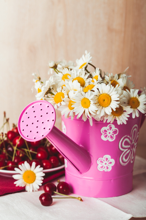 alongside: Bouquets of daisies inside rustic watering pot, on a white napkin and wooden background. Alongside is a plate full of cherries