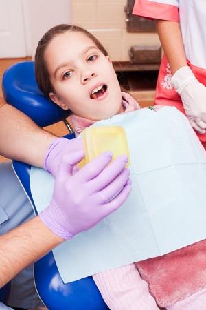 dental chair: A girl tries to establish a retainer for Teeth Dental Braces, sitting in a dental chair