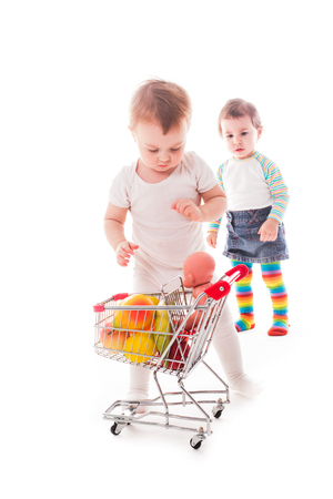 playing the market: Little girl plays with shopping trolley and doll. Grocery store playing