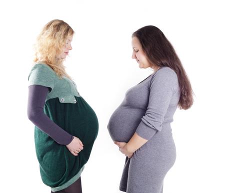 fondo para bebe: Dos mujeres embarazadas felices que esperan el nacimiento de sus bebés aislados sobre fondo blanco
