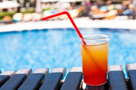 red straw: The orange refreshing cocktail with red straw near swimming pool