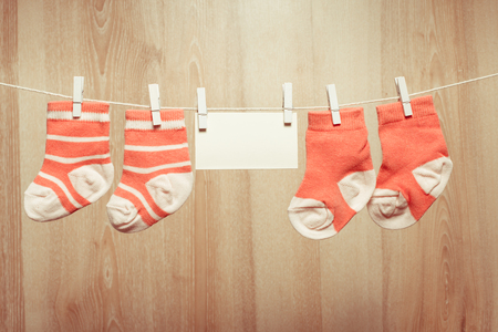 girl socks: Baby girl socks attached to the rope and blank card Stock Photo