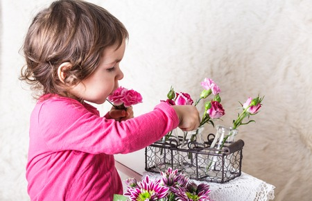 roleplaying: Little girl is smelling the roses. Playing the florist profession