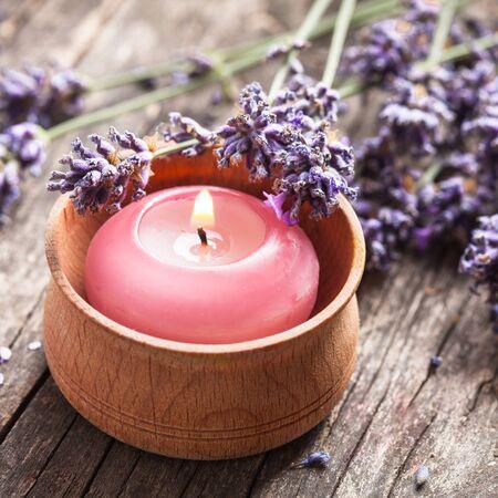 alongside: Sprig of fragrant lavender alongside a burning aromatic candle
