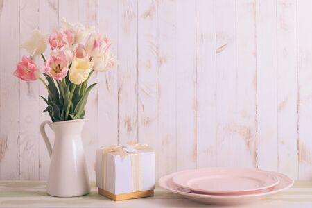 armful: White vase with delicate shades armful of tulips on a wooden background Stock Photo