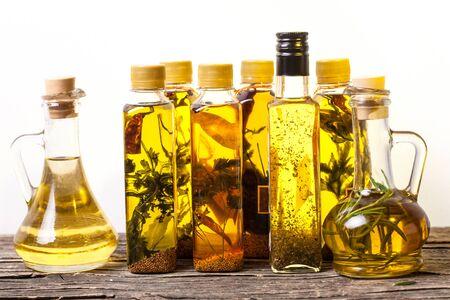 Assortiment d'huiles épicées avec des herbes et des épices dans différentes bouteilles sur fond blanc