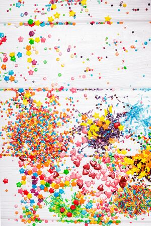 Various color sprinkles scattered on white wooden table