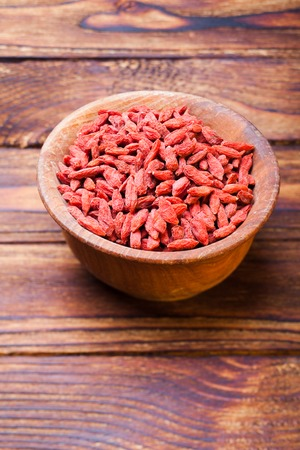 superfruit: Red dried goji berries in a wooden bowl