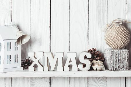 wall decor: Christmas decor on the shelf - wooden letters XMAS over wooden wall Stock Photo