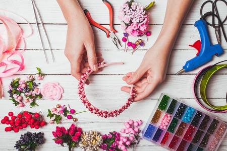 cintillos: bayas, flores de plástico, perlas e instrumentos para hacer cintas para el pelo hechos a mano. Vista superior con las manos Foto de archivo