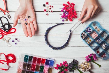 headbands: bayas, flores de pl�stico, perlas e instrumentos para hacer cintas para el pelo hechos a mano. Vista superior con las manos Foto de archivo