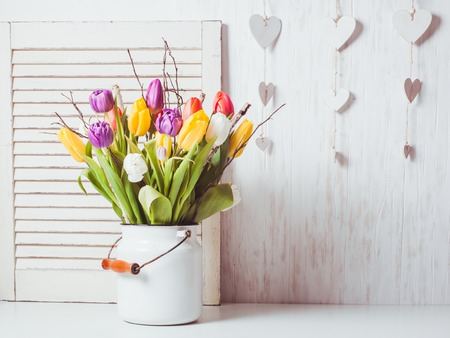 white cane: Color tulips with branches in a white cane. Spring decor