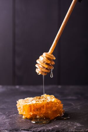 Honey drip and comb over black slate background