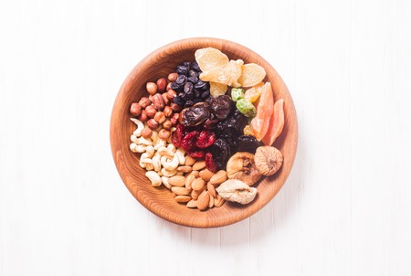 frutas secas: Dry fruits and nuts in bowl on wooden table. Copy space background - close up healthy sweets