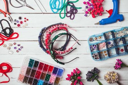 cintillos: bayas, flores de plástico, perlas e instrumentos para hacer cintas para el pelo hechos a mano. Vista superior Foto de archivo