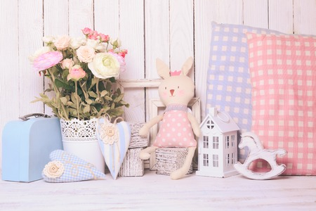 Small toy house, pony, toy bunny, pillows in  the children's room on wooden background