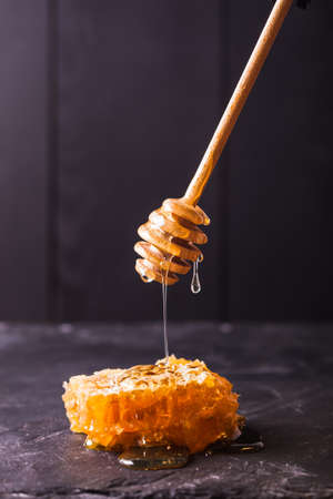 honey comb: Honey drip and comb over black slate background