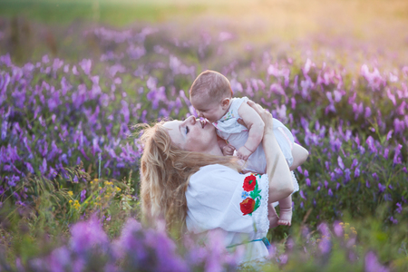 Beautiful young mother tenderly holding up her little adorable baby at sunset in a field Stock Photo