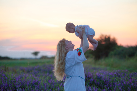 tenderly: Beautiful young mother tenderly holding up her little adorable baby at sunset in a field Stock Photo