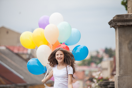 latex girl: Pretty girl with big colorful latex balloons posing in the street of an old town
