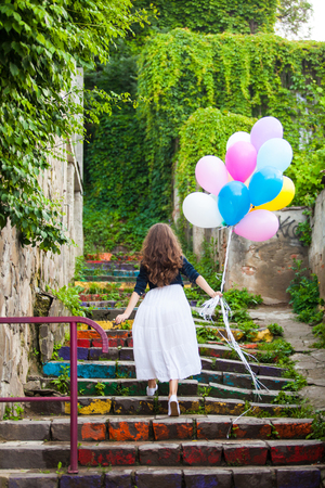 Pretty girl with big colorful balloons walking upstairs in old town