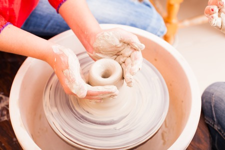 potters wheel: Hands of girl who tries to make pottery from white clay on a potters wheel