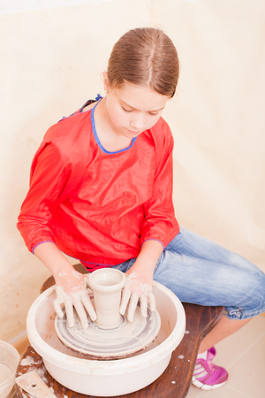 potters wheel: Portrait of girl who tries to make pottery from white clay on a potters wheel Stock Photo