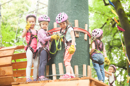 bridge in nature: Kids on obstacle course in adventure park in mountain helmet and safety equipment