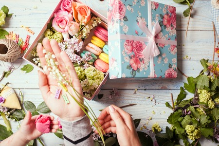 flower box: Preparation of flower box with macaroons, top view of florist workplace Stock Photo