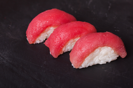 maguro: Close-up of Maguro sushi with tuna on a black slate background