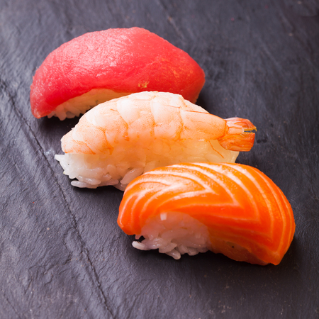 Close-up of set of tree sushi with salmon, tuna and shrimp on a slate