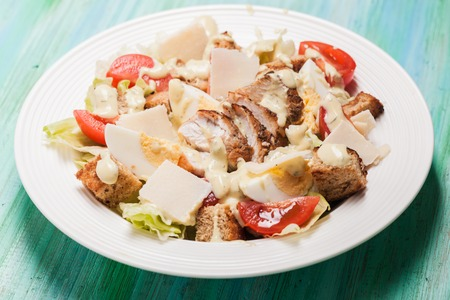 Salad Caesar in a white plate on the table