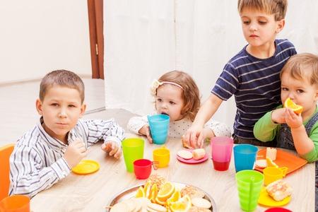 children party: Group of happy children enjoying party on birthday in kindergarten