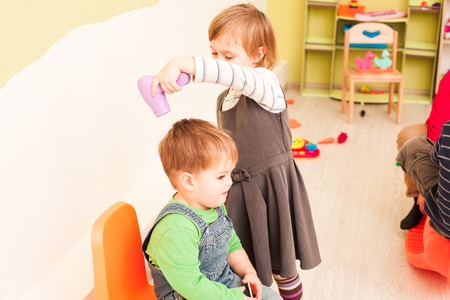 The children are playing a hairdresser game. The girl is holding a hairdryer and making a hairstyle for the boy Stock Photo