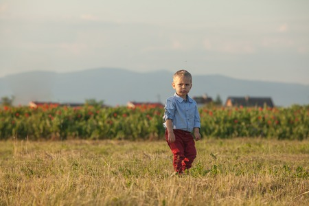 Portrait of a little cute boy in red pants on a rural background Stock Photo