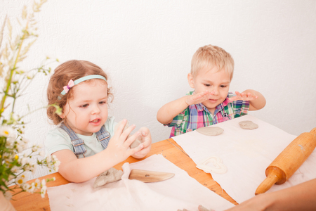 modelling clay: Little boy using a rolling pin that to roll modelling clay Stock Photo