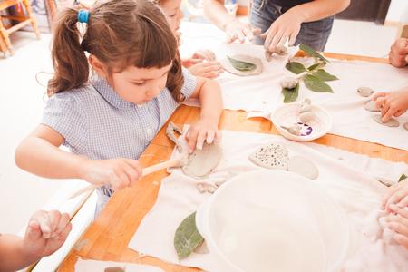 Cute children sculpt something from grey plasticine in kindergarten Imagens