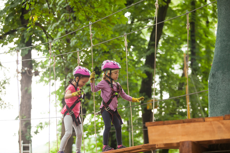 Kids on obstacle course in adventure park in mountain helmet and safety equipment