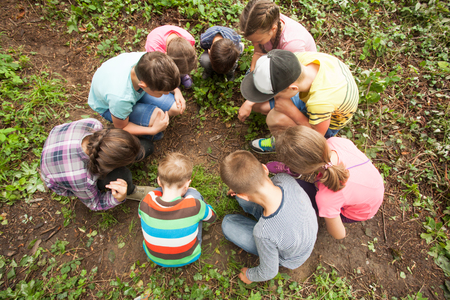 considering: A group of children who are considering something carefully, sitting in a circle on the background of nature Stock Photo