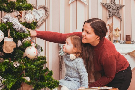 decorate: Young mom helping your little daughter decorating Christmas tree