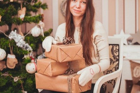 Girl in gloves holding  gift boxes on her knees near Christmas tree Stock Photo