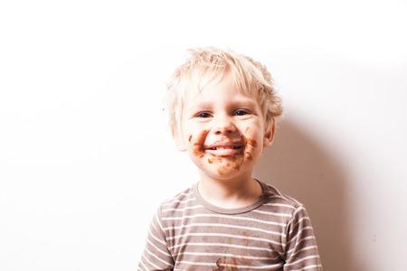 Portret van de blonde jongen met chocolade op zijn gezicht op wit wordt geïsoleerd Stockfoto - 65595289