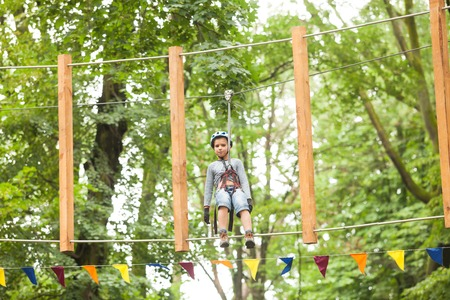 clambering: A boy in a helmet and safety equipment in adventure ropes park on the background of nature