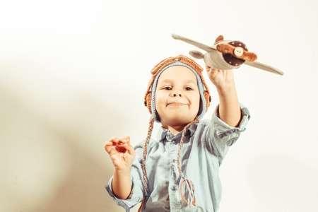 airman: Funny toddler boy in crochet pilot hat playing with textile airplane toy
