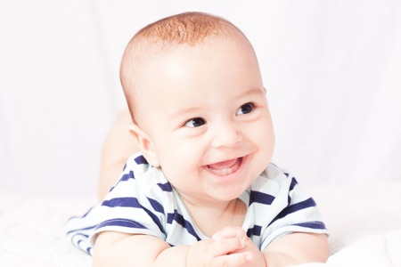 Portrait of a cute smiling baby that showing first milk or temporary teeth