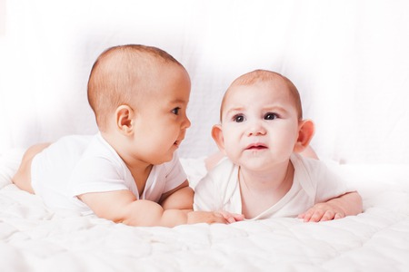 Two babies entertaining  each other and lying on the bad together Stock Photo