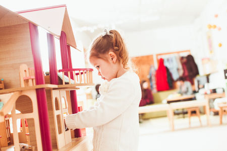 dollhouse: Girl playing with a dollhouse