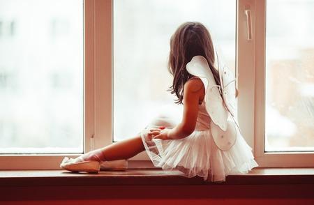 Dromerig meisje bij het raam