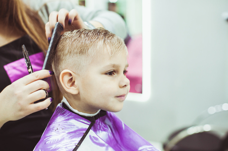 scissors: Little boy makes hairstyle at the hairdresser