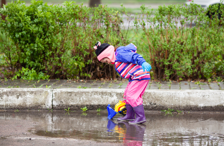 Little girl playing in the puddle Stock Photo